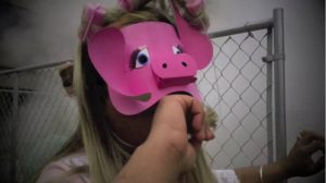 Anuj wearing a pink pig mask, biting his fist in front of a mesh fence.