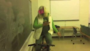 Anuj in his MIss Piggy mask riding a stationary bike in a classroom.
