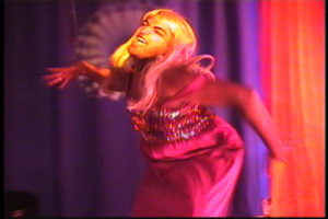 Anuj in a blond wig and sparkling pink dress, dancing in a frantic fashion.
