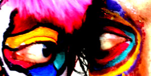 A close up of two faces, each covered in colorful make-up, looking at each other.