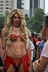 A gender performer in a long, curly blond wig wearing a red bikini with several layers of beads draped over them.