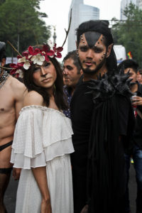 Two participants at Mexico City's Pride parade. One wears white and is made up to look like a fawn; the other dons all black and facial spikes.