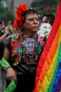A particpant in the Mexico City Pride parade wears a colorful leather vest sporting cultural patterns and holds a rainbow flag.