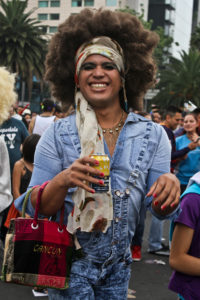 An individual in an all-denim disco outfit smiles into the camera while holding a drinkl, showcasing their pink nails which match their pink purse.