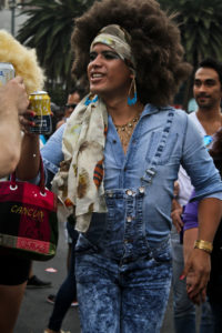 A candid shot of an individual wearing large hair tied back in a long headbnad, a denim button-down, and denim overalls.