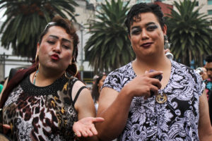 Two indiviuals in pedestrian clothing, one of whom blows a kiss to the camera. One wears a cheetah-print top and the other wears a black-and-white floral top.