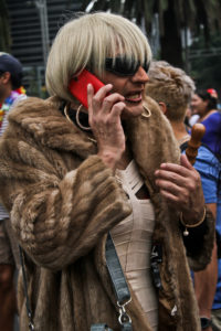 An individual wearing a heavy fur coat, a light colored dress, a short blond bob and with a red cell phone to their ear.