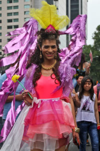 An individual wearing a bright pink dress with large, flowing purple wings on and a yellow crown-like headpiece smiles at the camera.