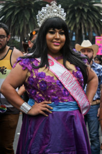 "A beautiful drag queen in a purple dress, crystal crown, and pink sash reading ""Mundo Mexico XXL 2016."""