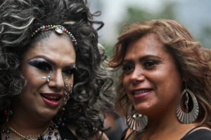 Two individuals looking at the camera while facing each other. One wears big curly black hair and heavy make-up, including many facial rhinestones, while the other wears feathered brown hair and large earrings with minimal make-up.