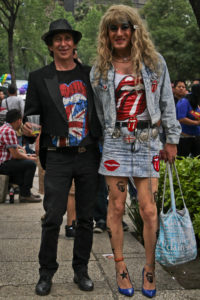 Two individuals each wearing Rolling Stones t-shirts. One wears short hair and black clothes, while the other wears a denim outfit with a short skirt and long blond wig.