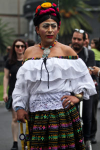 An individual wearing black hair in an updo fastened with colorful flowers, a shoulderless white top, and a black, green, and pink patterned skirt.