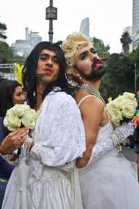 Two gender performers in white wedding gowns, standing back to back, looking near the camera while holding pale yellow roses. One wears a think brown beard and the other is cleanshaven.