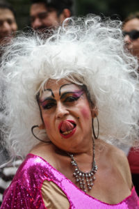 A close-up of the gender performer in exaggerated make-up and a white wig as they lick their lips.